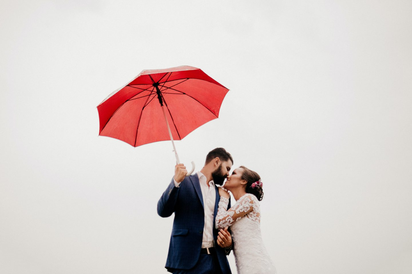 man and woman under red umbrella