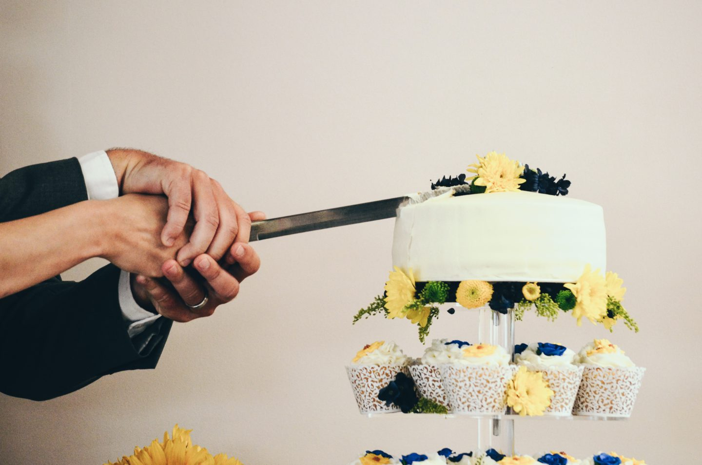 couple both holding knife slicing a cake on tray