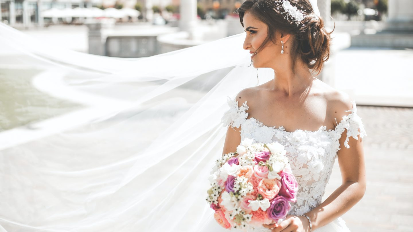 woman in white wedding dress holding bouquet of flowers